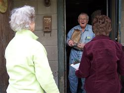 Volunteers delivering a meal to a senior